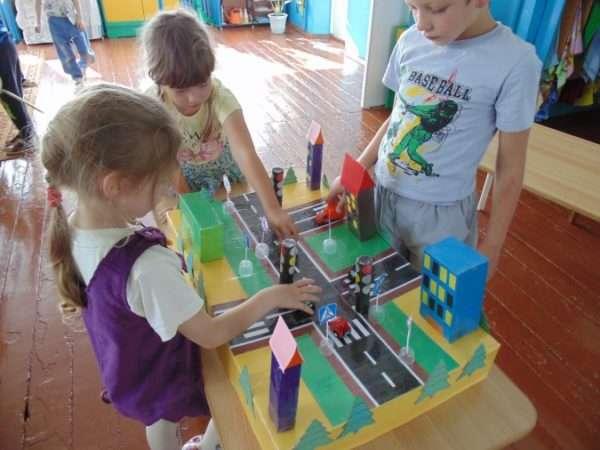 Две девочки и мальчик стоят над макетом улицы, девочка в фиолетовом сарафане что-то показывает