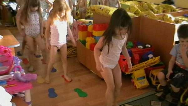 Дети идут по вырезанным из цветной бумаги следам