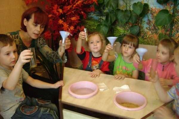 Дети и педагог держат в руках пробирки с жидкостью