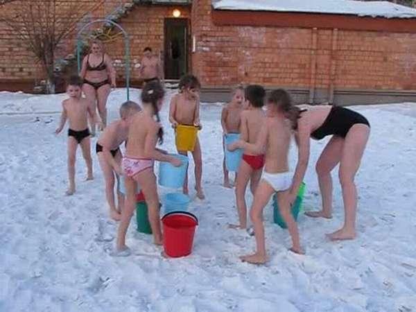 Дети с воспитательницей обливаются водой зимой
