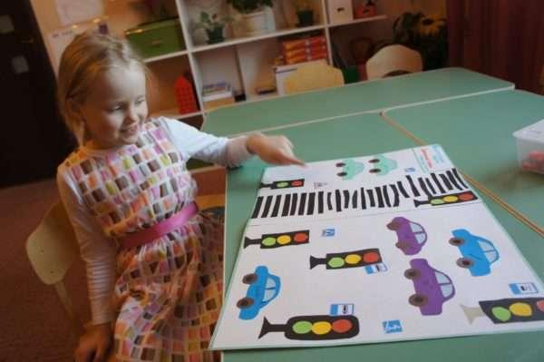 Девочка показывает на плакате с аппликацией по ПДД светофор