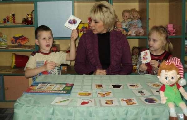 дети играют в печатную игру с педагогом