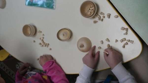 Двое детей играют в бирюльки