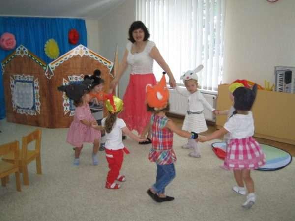 Дети в шапочках героев сказок и педагог водят хоровод