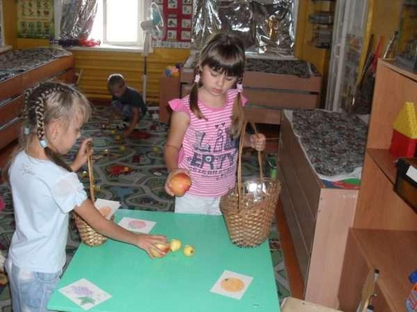 Две девочки играют в дидактическую игру «Овощи»