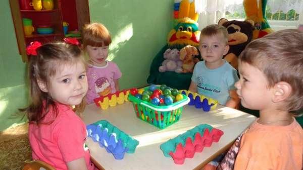 Четверо детей сортируют цветные шарики в картонные блоки для яиц подходящего оттенка