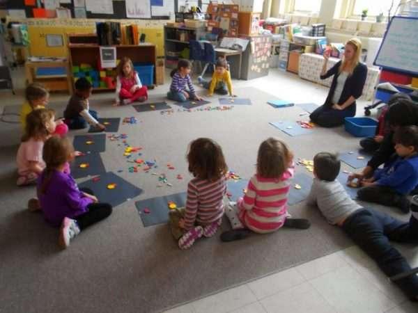 Дети и воспитательница сидят по кругу на полу, собирают картинку из фигур