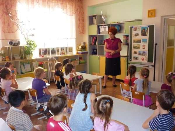 Дети сидят за партами, педагог стоит у доски с иллюстрациями к занятию