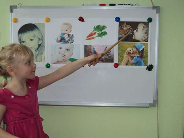 Девочка показывает указкой на картинки на магнитной доске