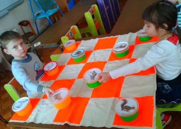 Мальчик и девочка играют в импровизированные шашки