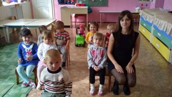 Воспитательница и дети сидят на стульях, как в автобусе