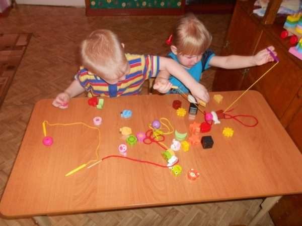 Мальчик и девочка сидят за столом и нанизывают фигурки на шнурок