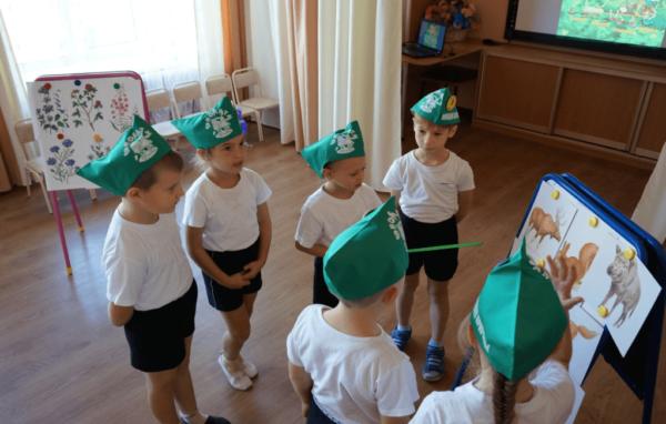 Дети в зелёных пилотках рассматривают картинки с животными